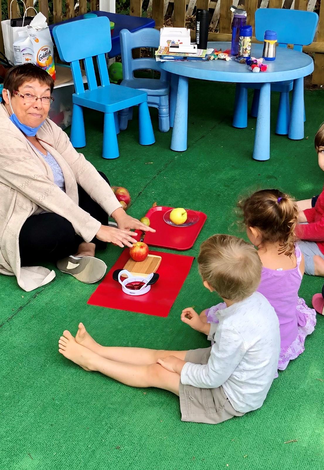 Women with children cutting apples